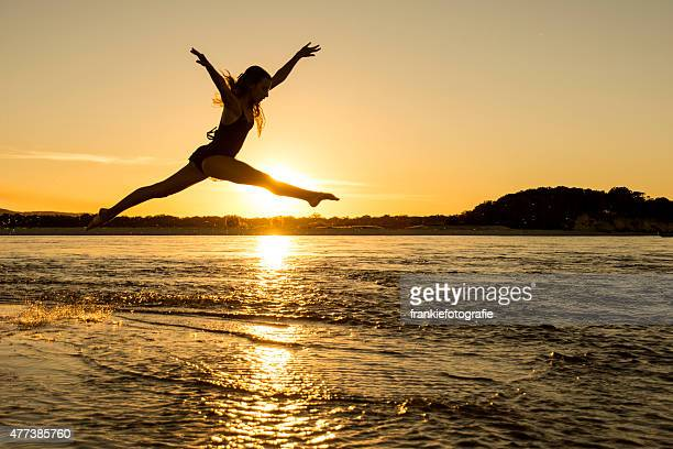 Girl jumping across water