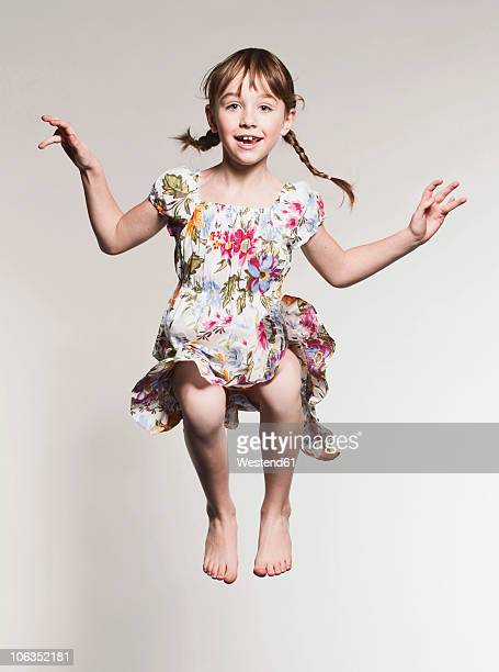 Girl (6-7) jumping against gray background, portrait, smiling