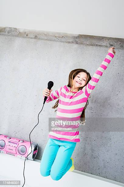 Girl jumping and singing on bed