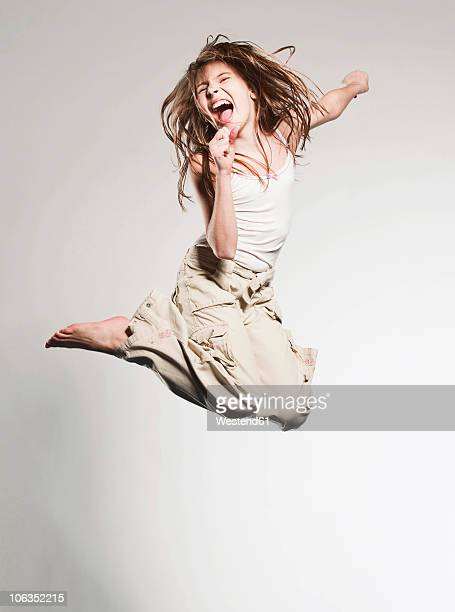 Girl (10-11) jumping and singing