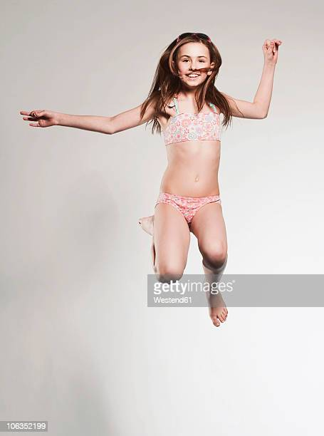 girl (10-11) jumping and smiling, portrait - 10 11 years stock photos and pictures