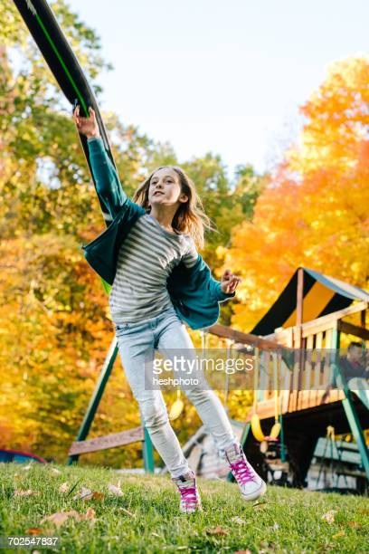girl jumping and throwing toy rocket in garden - heshphoto stock pictures, royalty-free photos & images