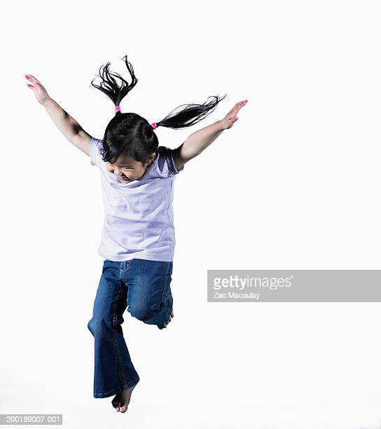 Girl (4-6) jumping, arms outstretched, smiling