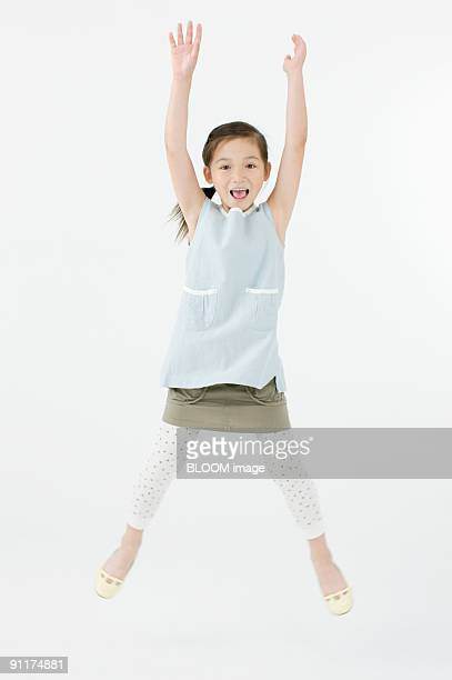 Girl jumping, arms raised