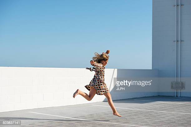 Girl jumping barefoot on building rooftop