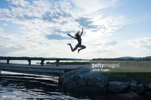Girl jumping by lake