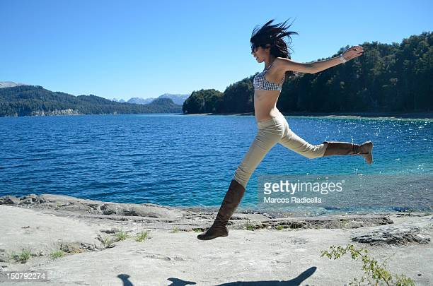 girl jumping by lakeside - radicella stock pictures, royalty-free photos & images