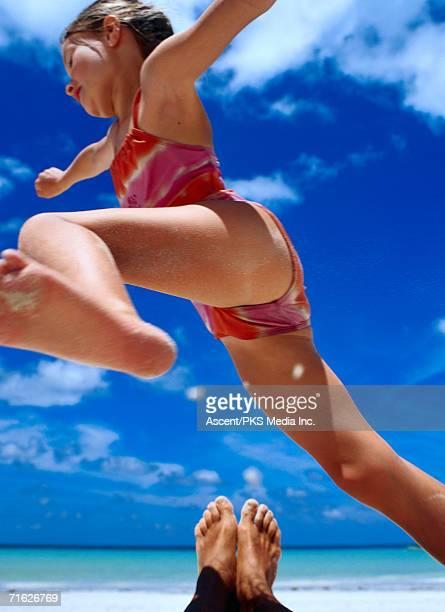 Girl jumping dad's legs, Seychelles