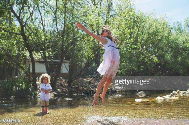 Girl jumping for joy out of water
