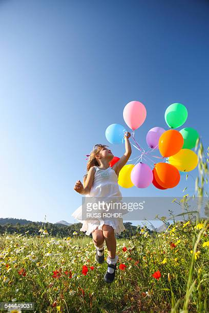 Girl jumping for joy with colorful balloons in wildflower meadow, Majorca, Spain