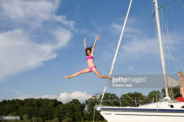 Girl jumping from boat into water
