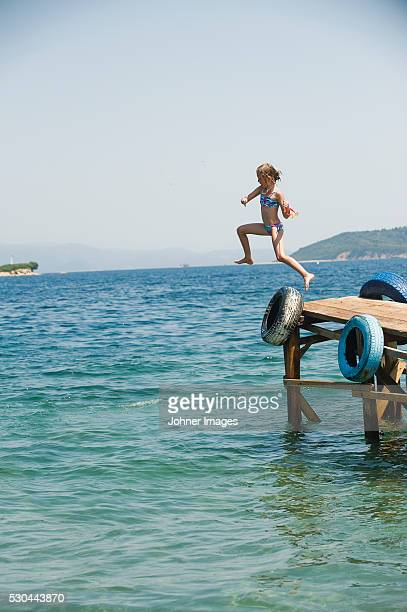 Girl jumping from jetty
