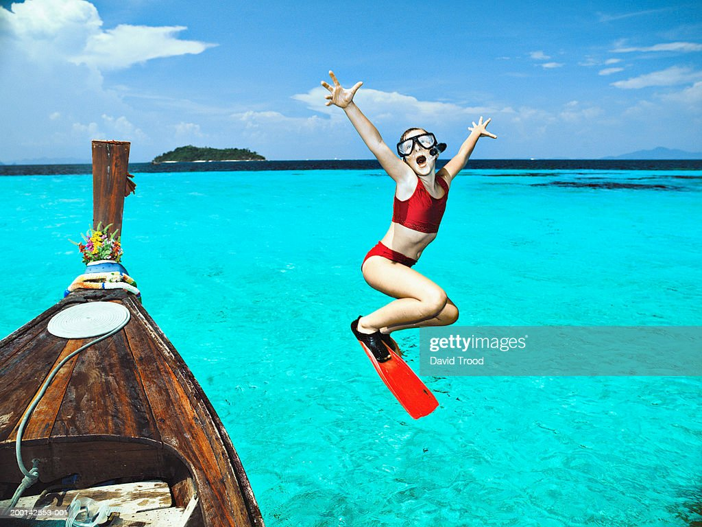Girl (9-11) jumping from longtail boat into sea : ストックフォト