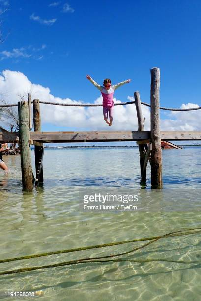 girl jumping from pier in sea against sky - emma hunter eye em stock photos and pictures