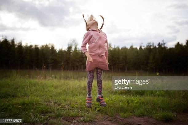 girl (6-7) jumping in a grassy meadow in a forest in germany - trädområde bildbanksfoton och bilder