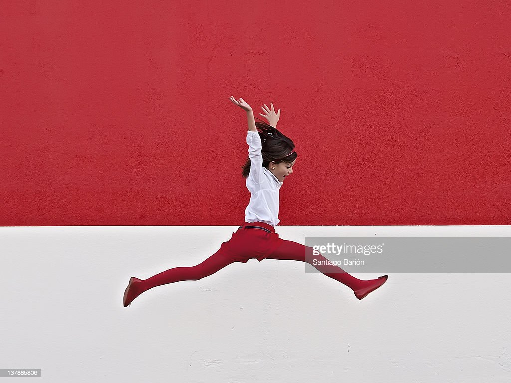 Girl jumping in air at red wall : Stock Photo