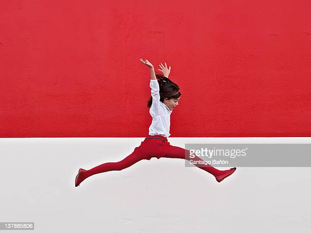 girl jumping in air at red wall - gegensatz stock-fotos und bilder