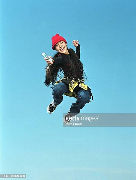 Girl (12-14) jumping in air, holding mobile phone, low angle, portrait