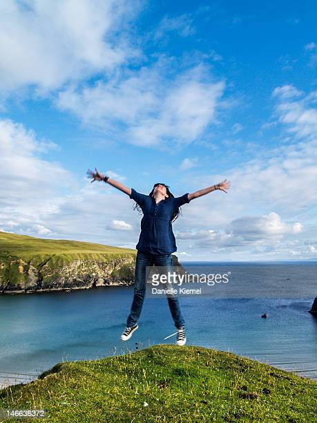 Girl jumping in air on sea cliff in Ireland