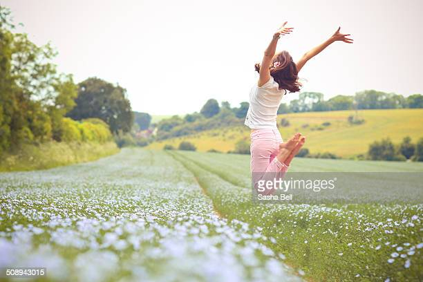 Girl Jumping in Blue Flaxseed Field