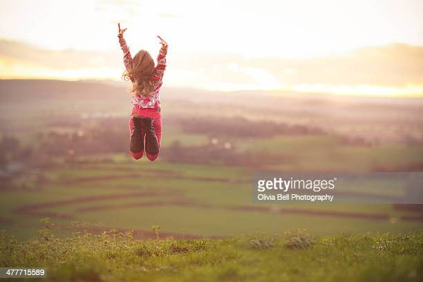 Girl Jumping in Field in Countryside