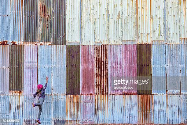 Girl jumping in front of a colorful corrugated metal wall, Kalgoorlie, Western Australia