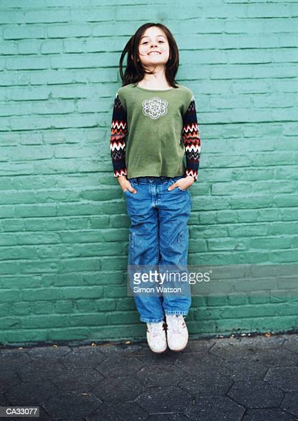 Girl (8-10) jumping in front of brick wall on street