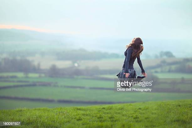 Girl Jumping in Green Field in Tartan Skirt