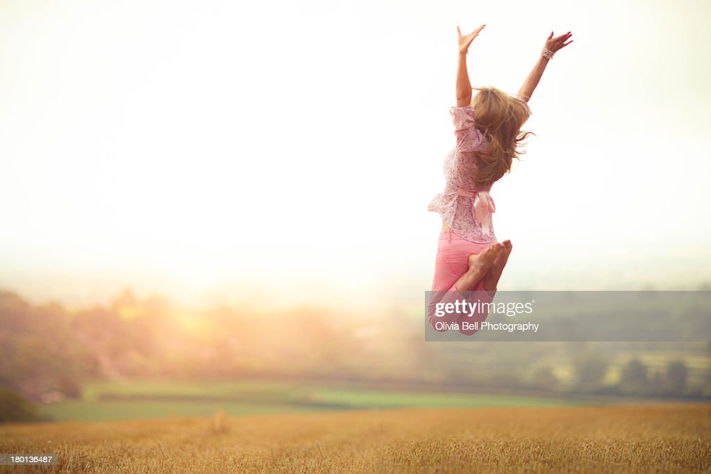 Girl Jumping in Harvested Wheat Field : Stock Photo