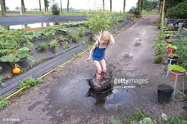 Girl jumping in muddy puddle in driveway