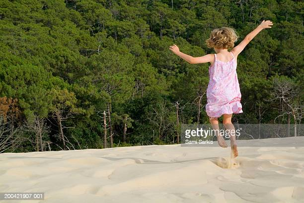 Girl (4-6) jumping in sand, arms outstretched, rear view