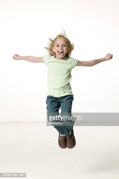 Girl (5-6) jumping in studio