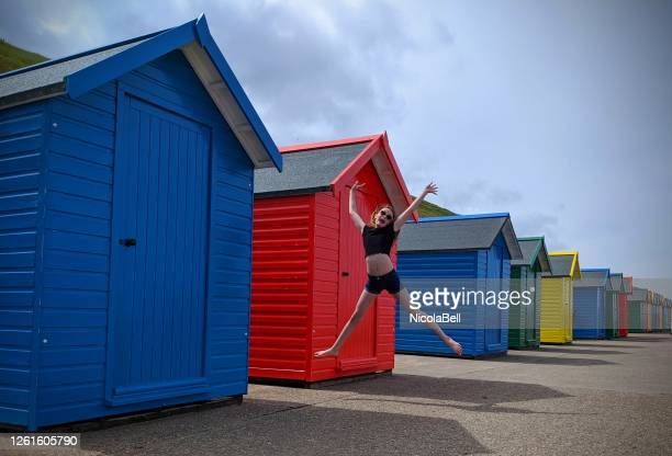 girl jumping in the air by beach huts, whitby, yorkshire, england, uk - legs apart stock pictures, royalty-free photos & images