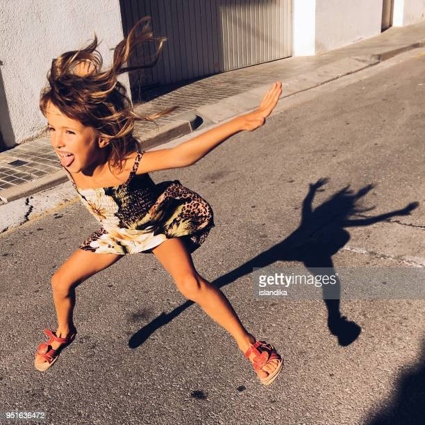 girl jumping in the street - taken on mobile device stock photos and pictures