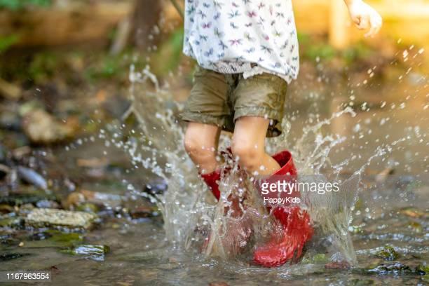 meisje springen in water - laars stockfoto's en -beelden