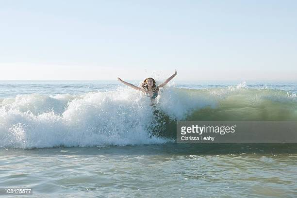 Girl jumping in wave