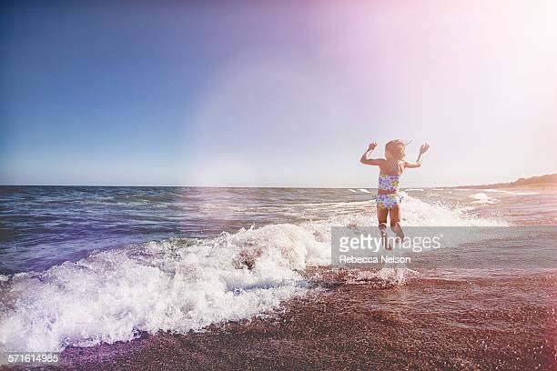 girl jumping in waves