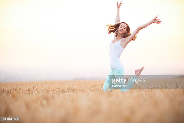 Girl jumping in wheat field