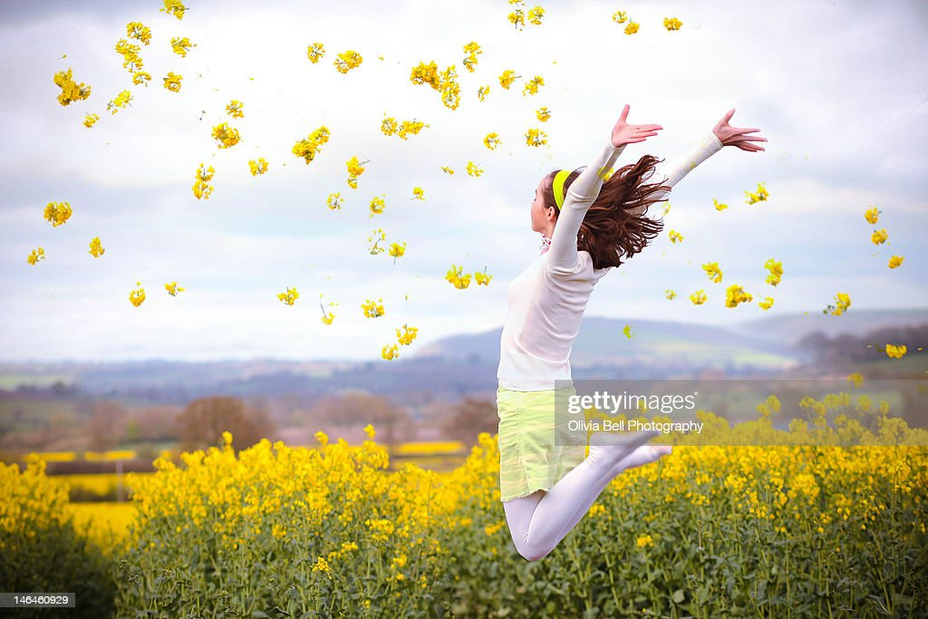 Girl jumping in yellow Rapeseed field : ストックフォト