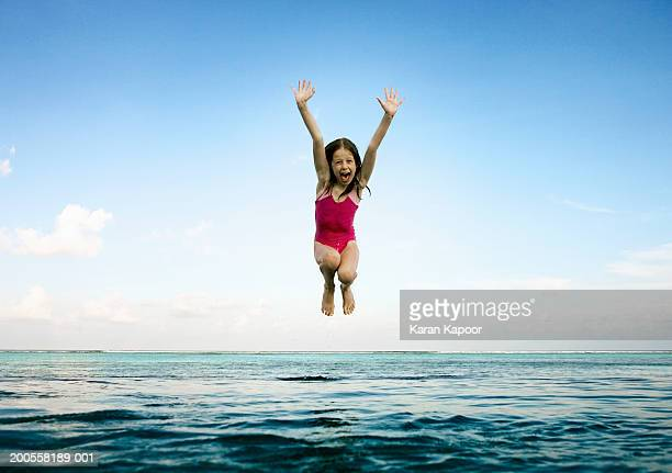 Girl (8-9) jumping into infinity pool, mouth Open