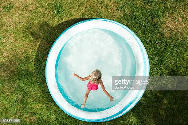 girl jumping into inflatable swimming pool, summer on dried grass - circle stock pictures, royalty-free photos & images