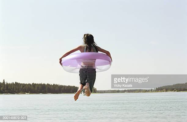 Girl (11-13) jumping into lake with inner tube, rear view
