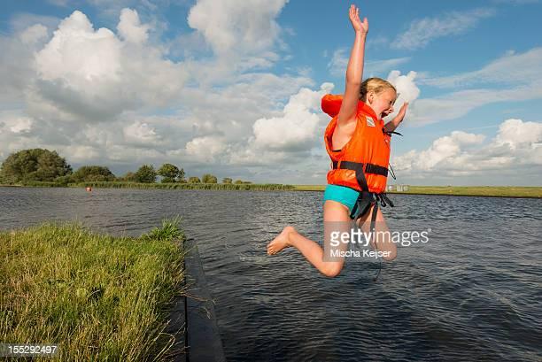 Girl jumping into rural lake