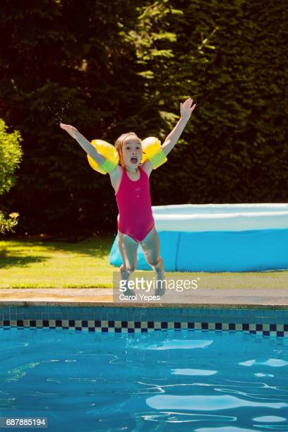 girl jumping into swimming pool in floatiesgirl jumping in swimming pool in floaties
