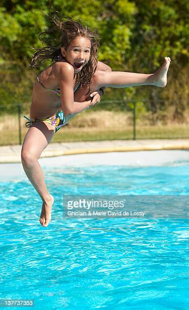 girl jumping into swimming pool - swimwear stock photos and pictures