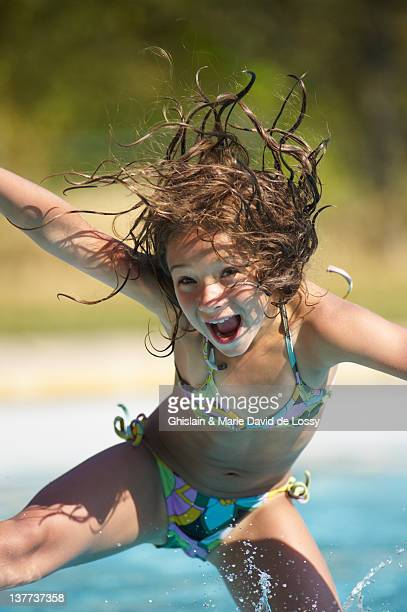 girl jumping into swimming pool - bikini stock pictures, royalty-free photos & images