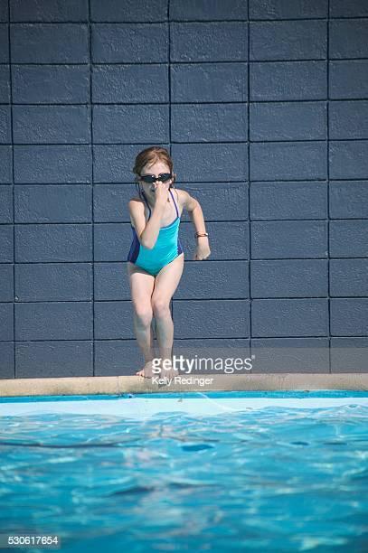 girl jumping into swimming pool - 鼻をつまむ ストックフォトと画像