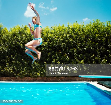 Girl Jumping Into Swimming Pool Side View Foto Stock Getty Images