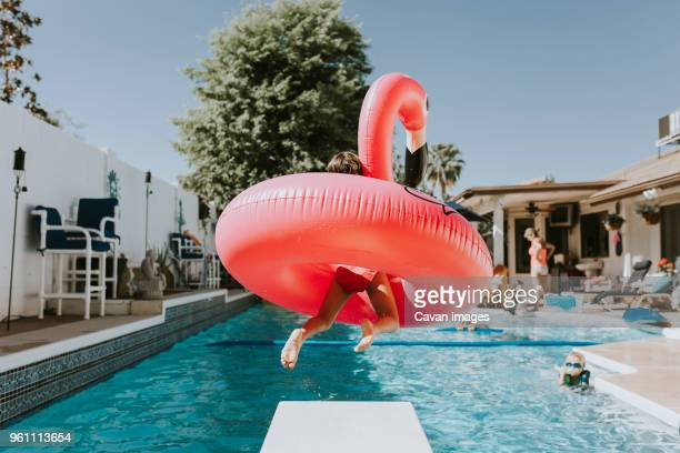 girl jumping into swimming pool with pink flamingo - flamingo stock photos and pictures