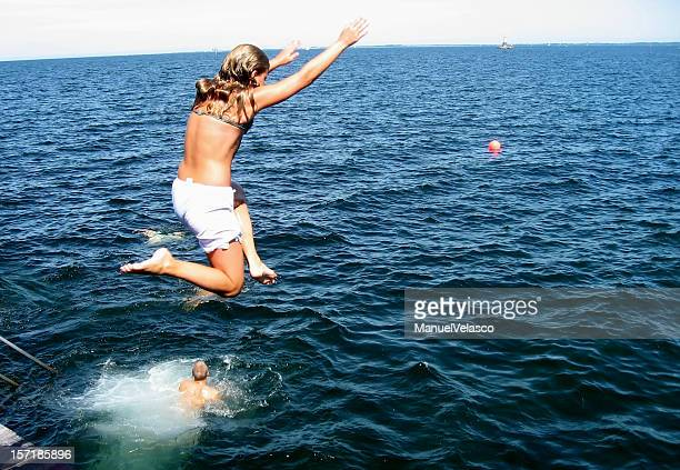 girl jumping into the sea